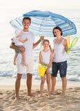 Hombre y mujer con dos niños que se unen bajo umbrel de la playa Imágenes de archivo libres de regalías