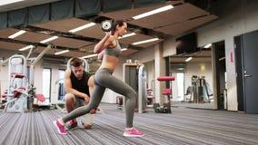 Hombre y mujer con el barbell que dobla los músculos en gimnasio metrajes