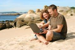 Hombre y mujer con el ordenador en la playa Imágenes de archivo libres de regalías