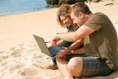 Hombre y mujer con el ordenador en la playa Fotos de archivo