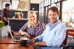 Hombre y mujer con el ordenador portátil en una cafetería foto de archivo libre de regalías