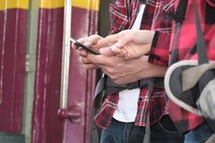 Hombre y mujer con el uso app de la mochila en smartphone en la estación de tren Foto de archivo libre de regalías