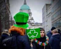 Hombre y mujer con la bandera verde del trébol en la celebración del día del ` s de St Patrick de la ciudad de Belfast Imagen de archivo libre de regalías