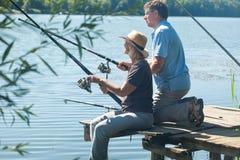 Hombre y mujer con las cañas de pescar Foto de archivo
