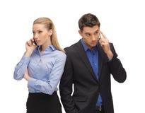 Hombre y mujer con los teléfonos celulares Imágenes de archivo libres de regalías