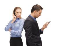 Hombre y mujer con los teléfonos celulares Imagenes de archivo