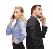 Hombre y mujer con los teléfonos celulares Fotos de archivo