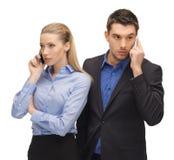 Hombre y mujer con los teléfonos celulares Imagen de archivo libre de regalías