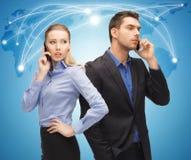 Hombre y mujer con los teléfonos celulares Fotos de archivo libres de regalías