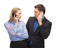 Hombre y mujer con los teléfonos celulares Fotografía de archivo libre de regalías