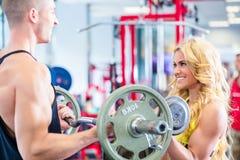 Hombre y mujer con pesas de gimnasia en gimnasio Imágenes de archivo libres de regalías