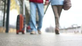 Hombre y mujer con una maleta que va en la plataforma de la estación de tren La gente se está preparando para subir al avión, cer almacen de video
