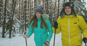 Hombre y mujer de amor en el esquí del invierno de la cámara lenta en el bosque que mira uno a que sonríe Día de tarjeta del día  almacen de metraje de vídeo