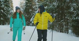 Hombre y mujer de amor en el esquí del invierno de la cámara lenta en el bosque que mira uno a que sonríe Día de tarjeta del día  metrajes