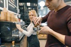 Hombre y mujer de Barista que hacen el café, par de la gente joven que trabaja en cafetería fotos de archivo