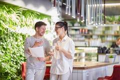 Hombre y mujer de comunicación en cafetería con los papeles foto de archivo libre de regalías