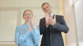 Hombre y mujer de dos hombres de negocios que aplauden en una oficina en un fondo de la ventana con los obturadores aplauso metrajes
