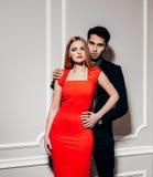 Hombre y mujer de la moda de los jóvenes contra la pared blanca, mirando la cámara Él la abraza de detrás indoor Color caliente foto de archivo