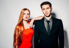 Hombre y mujer de la moda de los jóvenes contra la pared blanca, presentando para la cámara indoor Color caliente imágenes de archivo libres de regalías