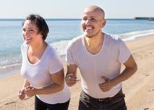 Hombre y mujer de mediana edad que corren en la playa Fotos de archivo libres de regalías