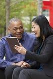 Hombre y mujer de negocios afuera en su rotura con sus tabletas Imagen de archivo