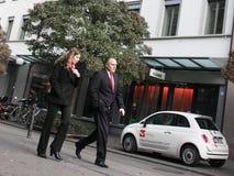 Hombre y mujer de negocios en trajes costosos que andan a trancos abajo del stre Imagen de archivo libre de regalías