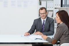 Hombre y mujer de negocios en una reunión Imagen de archivo libre de regalías