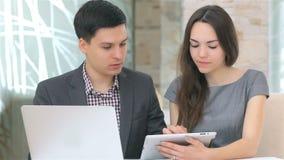 Hombre y mujer de negocios joven que discuten la compaginación almacen de video