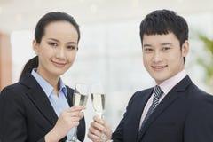 Hombre y mujer de negocios joven que tuestan con las flautas de champán imagen de archivo libre de regalías