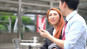 Hombre y mujer de negocios que discuten sobre su trabajo sobre móvil en la calle almacen de video