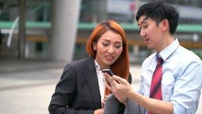 Hombre y mujer de negocios que discuten sobre su trabajo sobre móvil en la calle metrajes