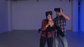 Hombre y mujer de risa en las auriculares de la realidad virtual que miran sus fotos divertidas en el teléfono Imagenes de archivo