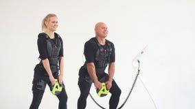 Hombre y mujer del ajuste en el traje muscular eléctrico para el estímulo con pesas de gimnasia almacen de metraje de vídeo