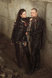 Hombre y mujer del asaltante entrenado para la lucha cuerpo a cuerpo en el traje de cuero con un arco en el mundo posts-apocalípt fotos de archivo libres de regalías