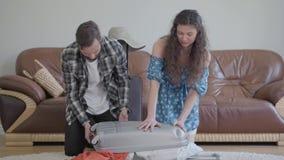Hombre y mujer del retrato que se sientan en el piso en casa delante del sof? de cuero, embalando una maleta antes de viaje all? metrajes