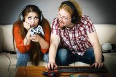 Hombre y mujer del videojugador de la PC con el cojín del juego Foto de archivo libre de regalías