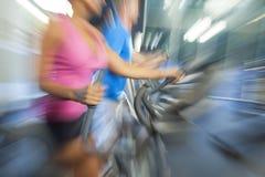 Hombre y mujer del zoom de la falta de definición de movimiento que usa el equipo de la gimnasia Foto de archivo libre de regalías