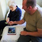 Hombre y mujer discutir la tecnología del iPhone y del iPad imagenes de archivo