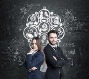Hombre y mujer e iconos del negocio en la pizarra Fotos de archivo libres de regalías
