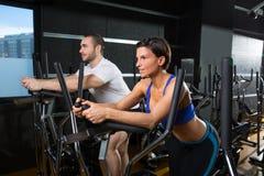 Hombre y mujer elípticos del instructor del caminante en el gimnasio negro Imagen de archivo libre de regalías