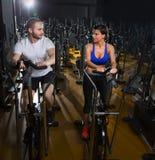 Hombre y mujer elípticos del instructor del caminante en el gimnasio negro Fotos de archivo libres de regalías