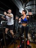 Hombre y mujer elípticos del instructor del caminante en el gimnasio negro Imagenes de archivo