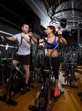 Hombre y mujer elípticos del instructor del caminante en el gimnasio negro Foto de archivo