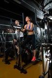 Hombre y mujer elípticos del instructor del caminante en el gimnasio negro Imágenes de archivo libres de regalías