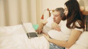Hombre y mujer embarazada de los jóvenes que usa su ordenador portátil en su dormitorio almacen de video
