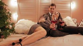 Hombre y mujer en amor abrazarse y beber el vino tinto en la cama en la cámara lenta de la atmósfera romatic del Año Nuevo metrajes