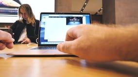 Hombre y mujer en Apple Store usando los ordenadores portátiles almacen de video