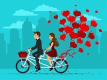 Hombre y mujer en el amor que monta una bici en tándem con los globos como corazones Foto de archivo