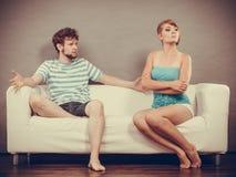 Hombre y mujer en el desacuerdo que se sienta en el sofá imagen de archivo