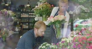 Hombre y mujer en el funcionamiento floral de la tienda almacen de video